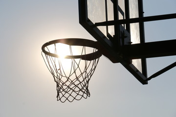Basketball hoop on basketball court under syn