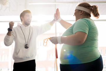 Waist up portrait of smiling fitness coach high fiving with fat young woman during workout in sunlight