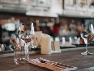 Empty glasses in the restaurant with knife and fork on wooden table, waiter prepare table to we;come customer