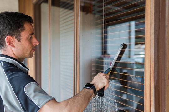 professional window washer wearing a smart watch while using squeegee to clean a window
