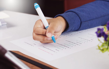 student's hand taking English test in class