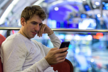 Caucasian man sitting indoors while using mobile phone