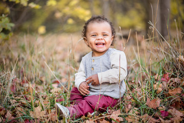 Outdoor Portrait of a beautiful smiling mixed race little boy. Adorable child with a very happy expression on his cute face