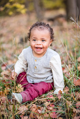 Outdoor Portrait of a beautiful smiling mixed race little boy. Adorable child laughing with a very cute expression on his face