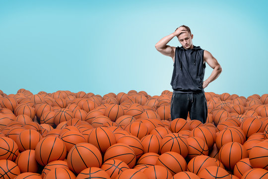 A thinking muscular man stands with one hand on a forehead in a field full of identical basketball balls.