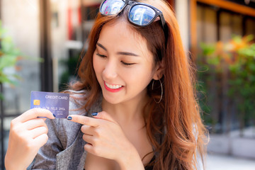 Attractive beautiful woman show and point finger to credit card. Charming beautiful young woman get satisfy and happy with freedom of payment. Gorgeous girl can bring the card instead money with smile