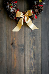 Christmas wreath made of pine cones on dark wooden background top view copy space