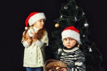 Merry children on Christmas eve decorate the Christmas tree . Children are dressed in warm sweaters and Santa hats