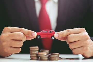 Business man in suit and close up hand holding model of toy car red on over a lot money of stacked coins - insurance, loan and buying car finance concept. buy and installments down payment  a car