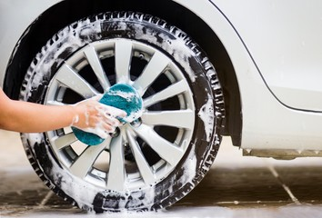 This image is a picture of wiping the car with a blue microfiber cloth by hands.Car wash concept.