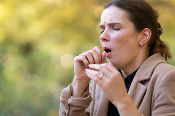 Young woman coughing or sneezing