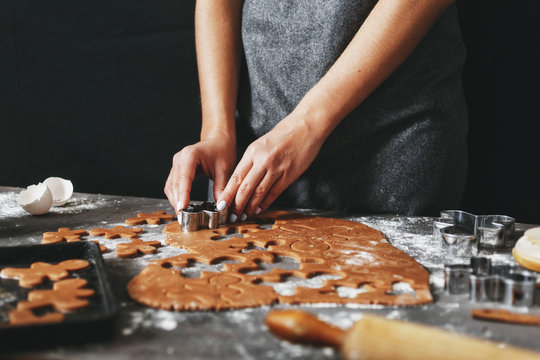 Woman preparing Christmas holiday cookies ginger men