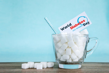 White sugar cube in a glass on wooden table with light blue background , unhealthy sweet food concept for 14th November campaign of World Diabetes Day