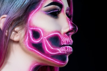 Halloween. Woman in day of the dead mask skull face art. Pink and black skull make up.