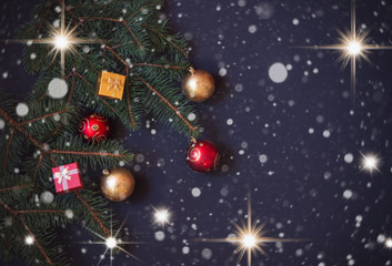 Christmas border made of fir branches, decorations and gifts on dark background.