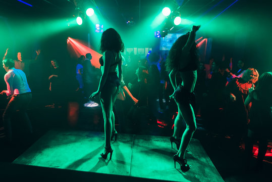 dancers dancing go-go on stage in a nightclub. Silhouettes of protruding girls
