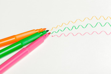 Three felt-tip pens of pink, orange and green color with drawn color marks on white background