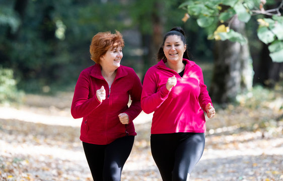 Mother and daughter wearing sportswear and running in forest