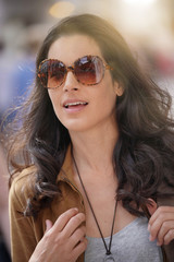Attractive brunette woman in town wearing sunglasses