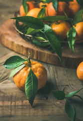 Christmas or New Year table. Fresh ripe tangerines with leaves in tray on board over rustic wooden table background, selective focus, vertical composition