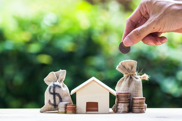 Saving money, home loan, mortgage, a property investment for future concept : A man hand putting money coin over small residence house and money bag.