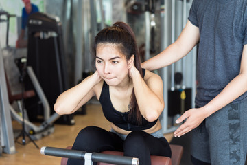 Attractive asian fitness woman doing exercise with her trainer.
