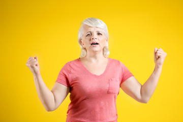 Portrait of emotional mature woman on color background