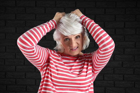 Portrait of stressed mature woman on dark background