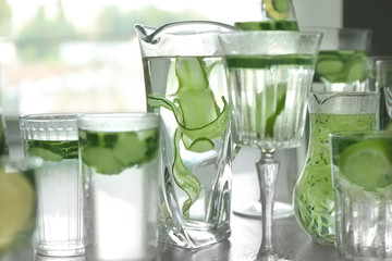 Glassware of fresh cucumber water on grey table