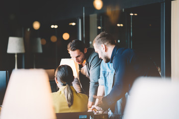 Startup and millenial business concept. Team of four people works together in big office. Woman explains new strategy plan