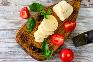 Mozzarella cheese with tomatoes and Basil on wooden background, top view