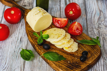 Mozzarella cheese with tomatoes and Basil on wooden background