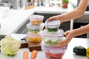 Woman holding stack of plastic containers with fresh vegetables for freezing at table in kitchen