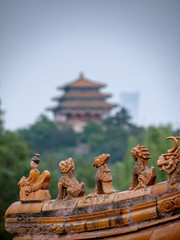 sculpture with Jingshan Park temple in background in Beijing