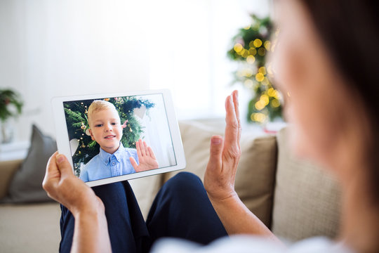 A grandmother with tablet making videocall with small grandson at Christmas time.