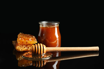 Jar of honey, wooden dipper and honeycomb against dark background