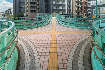 Crossing platform of a Manda pedestrian bridge with path for the blind in the center on Route 306 in the Kita district, north of Tokyo.