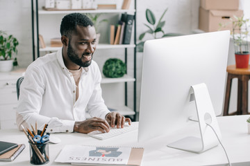 smiling handsome african american businessman working at computer in office