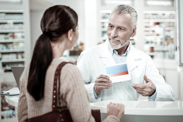 Pill box. Bearded mature pharmacist wearing white coat holding pill box while providing service his client