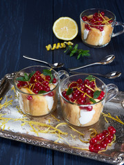 Three glass cups of limoncello (or limoncino) tiramisu topped with redcurrants and mint leaves, on a silver tray set on a dark background
