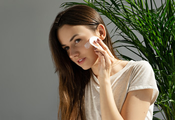 image of attractive girl applying cosmetic cream on her face