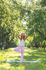 Beautiful girl doing yoga in the park. Stretching exercises