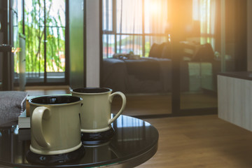 Twin white coffee or tea cup put on black table in comfortable room with sunrise lighting and copy space.