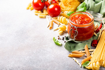 Glass jar with homemade classic spicy tomato pasta or pizza sauce with pine nuts and basil. Italian healthy food background. Copy space.