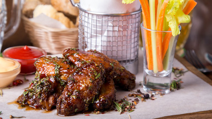 Barbecue chicken wings  on wooden tray with french fries and vegetables. Closeup