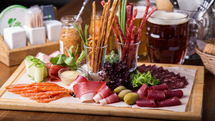 Delicious salami, pieces of sliced ham and  sausages on a tray. Cold meat  appetizer on a wooden tray