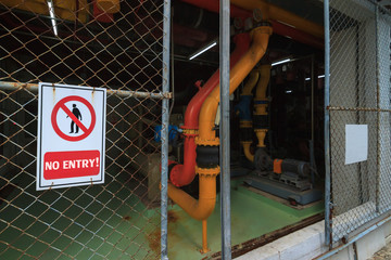 image of No entry sign was stick at the gate of restricted area. Mesh door of chiller control unit zone was open because the staff forgot to close background. Selective focus.