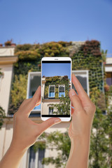 A tourist is taking a photo of a city garden on the facade of one of the houses in Rome, Italy on a mobile phone