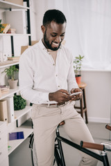 cheerful handsome african american businessman sitting on bike and using smartphone in office