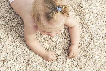 Adorable cheerful baby crawling on the pebble beach